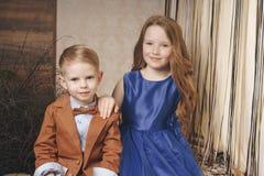 Två förskole- barn pojke och flicka sitter tillsammans på det utomhus- i staden i förhållande royaltyfri foto