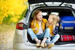 Två förtjusande flickor som sitter i en bilstam, innan att gå på semestrar med deras föräldrar Två ungar som framåtriktat ser för royaltyfri fotografi