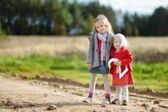 Två förtjusande lilla systrar som rymmer de stora TVÅNA Arkivbilder