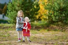 Två förtjusande lilla systrar som rymmer de stora TVÅNA Royaltyfri Fotografi