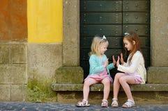 Två förtjusande lilla systrar som skrattar och kramar Arkivfoton