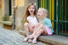 Två förtjusande lilla systrar som skrattar och kramar Arkivfoto
