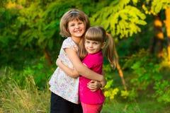 Två förtjusande lilla systrar som skrattar och kramar på solig dag royaltyfri foto