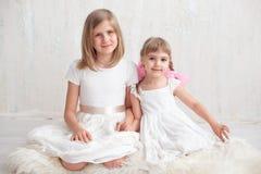 Två förtjusande lilla systrar som skrattar och kramar sig Arkivbilder