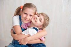 Två förtjusande lilla systrar som skrattar och kramar sig Arkivbild