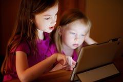 Två förtjusande lilla systrar som spelar med en digital minnestavla Royaltyfri Bild