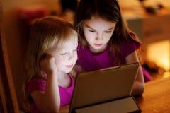 Två förtjusande lilla systrar som spelar med en digital minnestavla Royaltyfri Fotografi