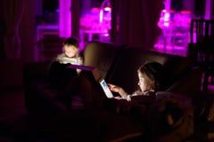 Två förtjusande lilla systrar som spelar med en digital minnestavla i ett mörkt rum Royaltyfri Foto