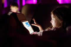 Två förtjusande lilla systrar som spelar med en digital minnestavla i ett mörkt rum Royaltyfria Foton