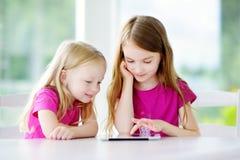 Två förtjusande lilla systrar som spelar med en hemmastadd digital minnestavla Barn i en grundskola Royaltyfri Bild