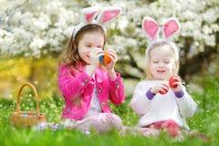 Två förtjusande lilla systrar som spelar med påskägg på påskdag Royaltyfri Foto