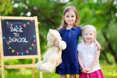 Två förtjusande lilla systrar som tillbaka går till skolan Arkivbild