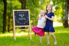 Två förtjusande lilla systrar som tillbaka går till skolan Arkivfoto