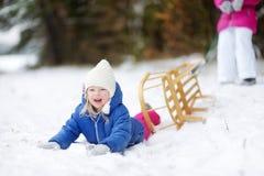 Två förtjusande lilla systrar som tycker om sleight, rider på vinterdag Arkivbild
