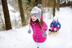 Två förtjusande lilla systrar som tycker om sleight, rider på vinterdag Arkivfoton