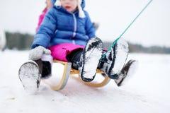 Två förtjusande lilla systrar som tycker om sleight, rider på vinterdag Arkivbilder