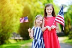 Två förtjusande lilla systrar som utomhus rymmer amerikanska flaggan på härlig sommardag Royaltyfri Fotografi