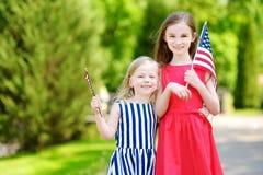 Två förtjusande lilla systrar som utomhus rymmer amerikanska flaggan på härlig sommardag Arkivfoto