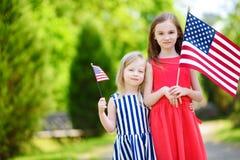 Två förtjusande lilla systrar som utomhus rymmer amerikanska flaggan på härlig sommardag Arkivfoton