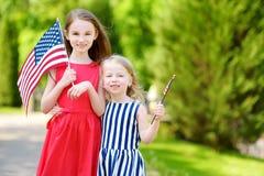 Två förtjusande lilla systrar som utomhus rymmer amerikanska flaggan på härlig sommardag Fotografering för Bildbyråer