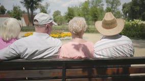 Två förtjusande mogna par som sitter på bänken och tillsammans talar Moget folk som vilar det fria gladlynt pension?r stock video