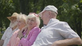 Två förtjusande mogna par som talar och ler sammanträde på bänken i sommaren, parkerar Dubbelträff av höga par arkivfilmer