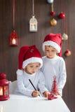 Två förtjusande pojkar som skrivar brevet till jultomten Royaltyfri Foto