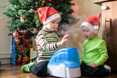 Två förtjusande pojkar som spelar med den funktionsdugliga luftfuktaren, väntande på x-mas Royaltyfri Fotografi