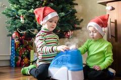 Två förtjusande pojkar som spelar med den funktionsdugliga luftfuktaren, väntande på x-mas Fotografering för Bildbyråer