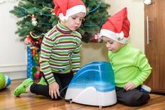 Två förtjusande pojkar som spelar med den funktionsdugliga luftfuktaren, väntande på x-mas Arkivfoton