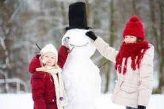 Två förtjusande små flickor som bygger en snögubbe i härlig vinter, parkerar tillsammans Gulliga systrar som spelar i en snö Fotografering för Bildbyråer