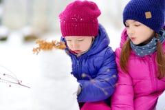 Två förtjusande små flickor som bygger en snögubbe i härlig vinter, parkerar tillsammans Gulliga systrar som spelar i en snö Royaltyfri Fotografi