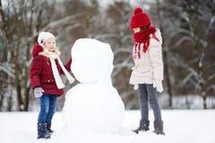Två förtjusande små flickor som bygger en snögubbe i härlig vinter, parkerar tillsammans Gulliga systrar som spelar i en snö Royaltyfri Bild