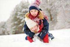 Två förtjusande små flickor som har gyckel i härlig vinter, parkerar tillsammans Härliga systrar som spelar i en snö royaltyfri bild