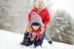 Två förtjusande små flickor som har gyckel i härlig vinter, parkerar tillsammans Härliga systrar som spelar i en snö royaltyfri foto