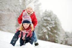 Två förtjusande små flickor som har gyckel i härlig vinter, parkerar tillsammans Härliga systrar som spelar i en snö royaltyfri fotografi