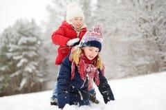 Två förtjusande små flickor som har gyckel i härlig vinter, parkerar tillsammans Härliga systrar som spelar i en snö arkivfoton