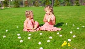 Två förtjusande små flickor som har gyckel med påsk Royaltyfri Foto