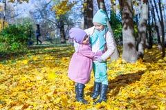 Två förtjusande små flickor som har gyckel på hösten Arkivbilder