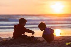 Två förtjusande ungar som spelar på stranden med sand arkivbild