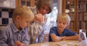 Två förtjusande vita barn som gör kakor med mormodern arkivbilder