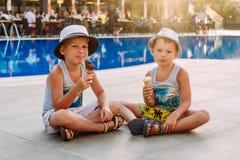 Två förträningspojkar i hattar sitter vid hotellets utomhus- pöl och äter glass i en dillandekotte kr?m- isungar Kanter i is arkivfoto