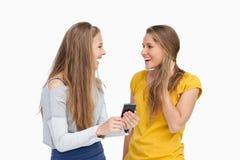 Två förvånade unga kvinnor som rymmer en smartphone Royaltyfri Bild