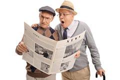 Två förvirrade höga män som läser nyheterna Arkivfoto