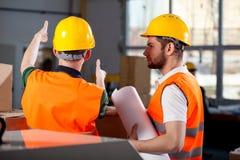 Två fabriksteknikerer som diskuterar arkivfoto