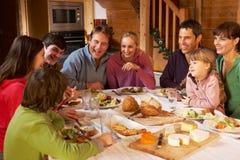 Två Familes som tycker om mål i alpin Chalet Royaltyfria Foton