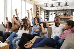 Två familjer som håller ögonen på sportar på television och att hurra Arkivfoton