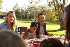 Två familjer som har en picknick i en parkera, över skuldrasikt arkivfoton