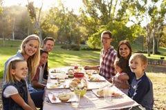 Två familjer som har en picknick på en tabellblick till kameran arkivfoto