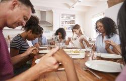 Två familjer som säger Grace Before Eating Meal Together arkivbilder